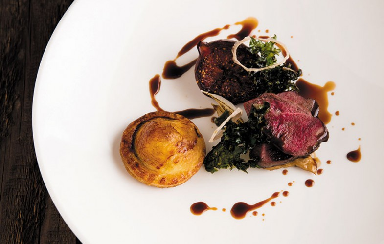 Roasted wood pigeon with confit pigeon pithivier, mushroom fricassee, kale and red wine-baked figs