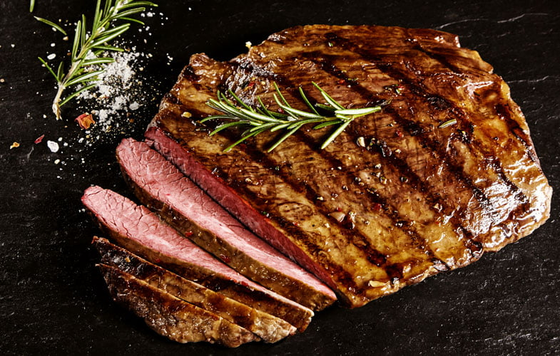 Marinated flank steak of beef with rosemary and rock salt wedges