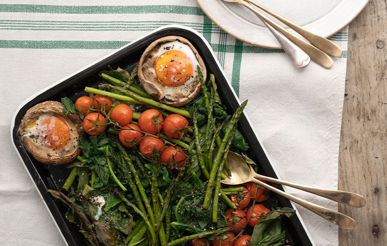 Portobello mushrooms baked with a fried egg inside, with roasted sweet cherry tomatoes and asparagus